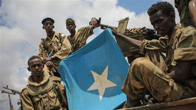 Des soldats somaliens montrent le drapeau somalien lors de leur arrivée à Saamoja, près de Kismayo.