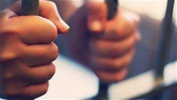 Les mains d'un détenu sur les barreaux d'une cellule