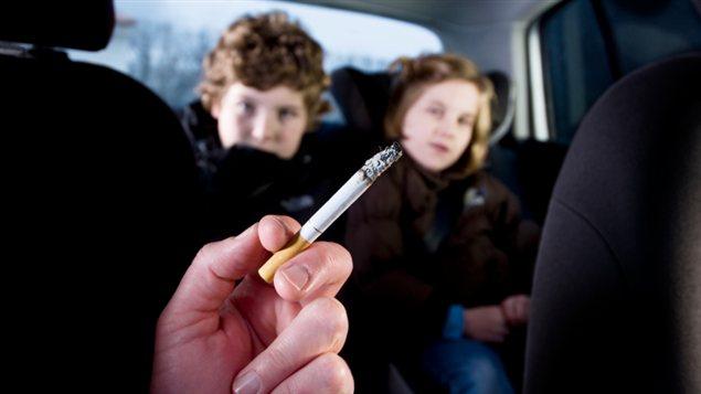 Une femme fume dans une voiture dont certains passagers sont des enfants.
