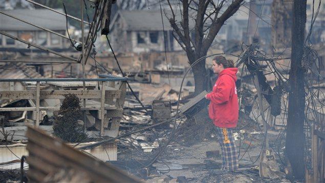 Une femme contemple les débris de sa maison rasée par les flammes qui ont détruit plus de 80 maisons dans le quartier de Queens, à New York.
