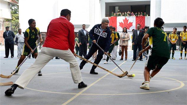 Le premier ministre Stephen Harper dispute un match de hockey-balle en Inde.