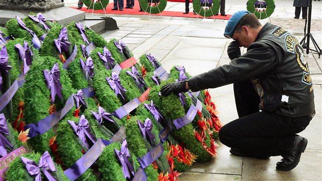 À Ottawa, un vétéran dépose, ému, une couronne en mémoire de soldats disparus.