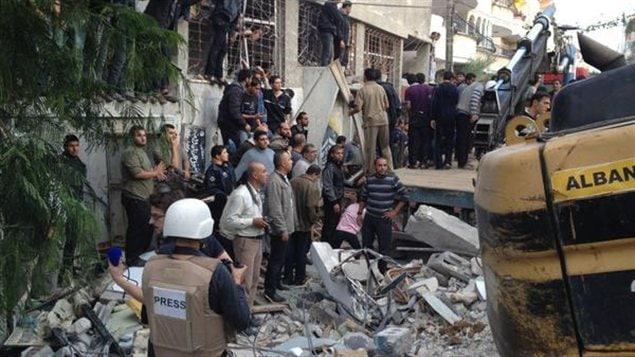Un journaliste observe un immeuble touché par une frappe israélienne à Gaza