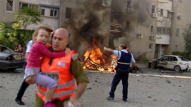 Un soldat israélien évacue une jeune fille d'un site touché par une roquette lancée depuis la bande de gaza dans le sud d'Israël.
