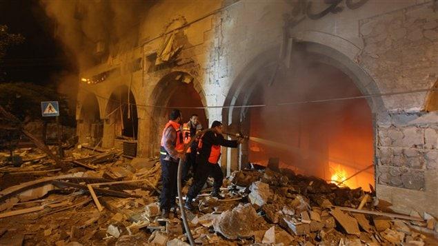 Les pompiers palestiniens tentent de maîtriser l'incendie qui a pris naissance après un raid israélien contre la Banque nationale islamique dans la ville de Gaza.