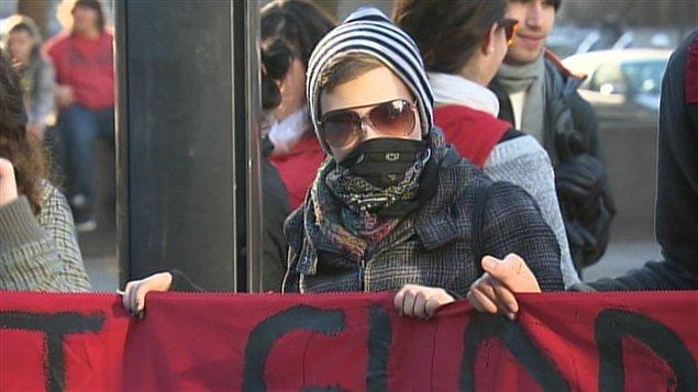 Un manifestant tenant avec ses pairs une bannière sur laquelle on peut lire : «La crise est globale, la lutte est mondiale, résistance générale.»