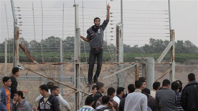 De jeunes Palestiniens lors d'une manifestation près d'une barrière de sécurité à la frontière de Gaza avec Israël, à l'est de Khan Younès, dans le sud de la bande Gaza le 23 novembre.