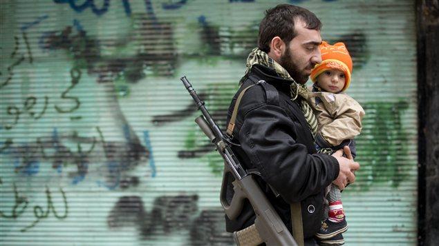 À Alep, un rebelle oprtant son fils
