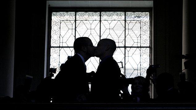 Un couple gai s'embrasse après avoir échangé es voeux à San Francisco.