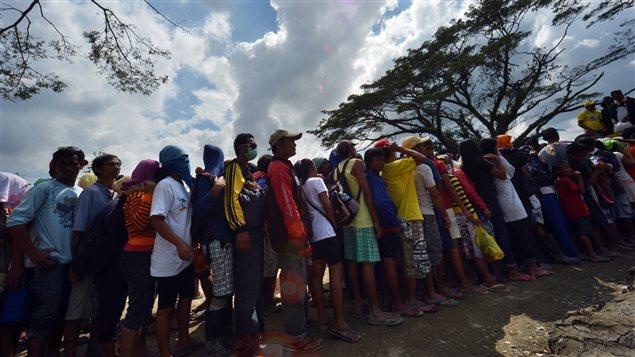 Des Philippins sinistrés après le passage du typhon faisaient la queue pour avoir de la nourriture, dimanche à New Bataan, dans le sud du pays.