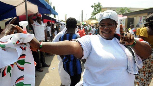 Une femme danse devant les quartiers généraux du parti Congrès démocratique national, de John Mahama.