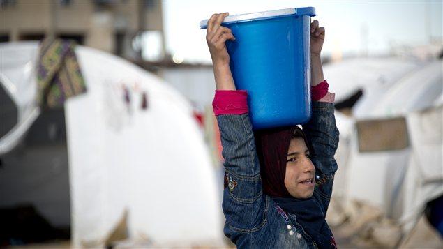 Une enfant transporte de l'eau dans un camp de réfugiés