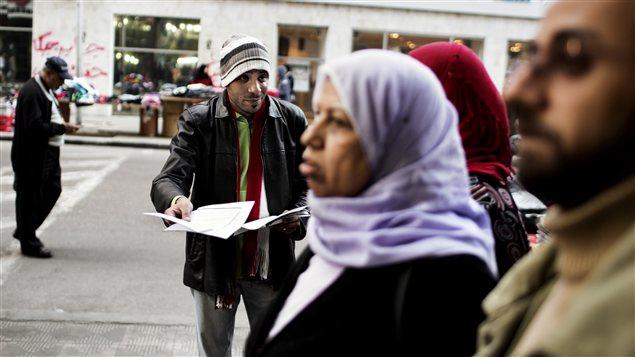 Un opposant distribuant des tracts appelant à voter contre le projet de constitution.