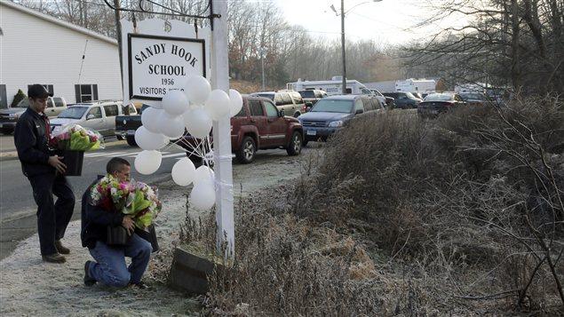 Des gens déposent des fleurs près de l'école primaire de Newtown où s'est déroulée la tuerie.