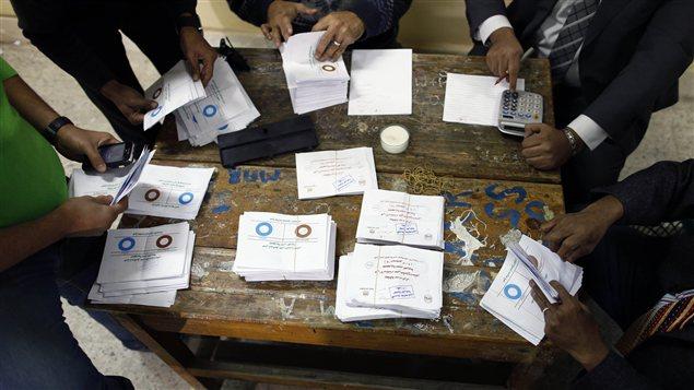 Des officiels procèdent au décompte des bulletins de vote, après le premier jour de vote sur le projet de Constitution en Égypte.