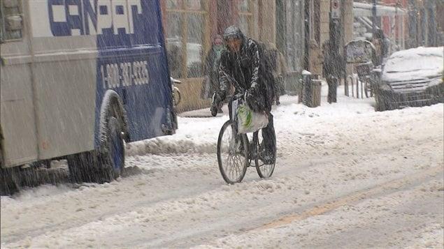 Un cycliste roule dans la neige dans une rue de Montr�al