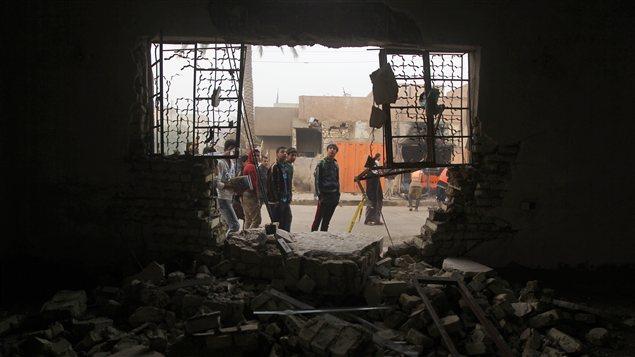 Des Irakiens observent les dommages subis par un édifice après un attentat survenu en novembre 2012, à Bagdad