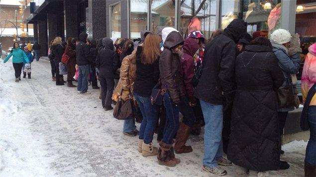 Une cinquantaine d'acheteurs en quête d'aubaines font la file par -30 Celcius devant le magasin Lululemon de Saskatoon le 26 décembre.