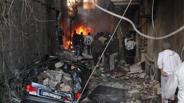 Des Syriens inspectent la scène d'une explosion à Jaramana le 28 novembre 2012.