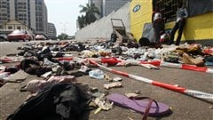 IVORY COAST, Abidjan : People stand next to clothing and various items spread over the pavement at the scene following a stampede in Abidjan, on January 1, 2013. At least 60 people died and at least dozens were injured as crowds stampeded overnight during celebratory New Year's fireworks, Ivory Coast rescue workers said on January 1, 2013. AFP PHOTO/HERVE SEVI