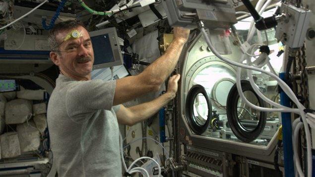 L'astronaute Chris Hadfield effectuant une expérience dans la Station spatiale internationale.