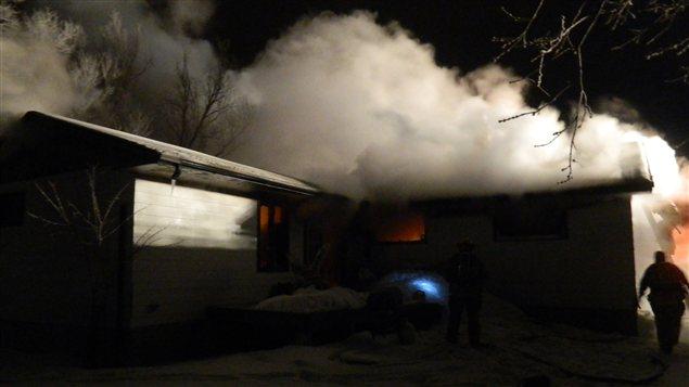 Des pompiers combattent un incendie dans une résidence de Gimli au Manitoba, tôt le matin du 1er janvier 2013.