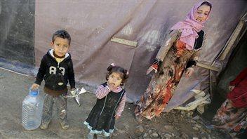 Des réfugiés syriens attendent à côté de leurs abris de fortune dans un champ de Saadnayel, dans la vallée de la Bekaa, au Liban, le 12décembre 2012.