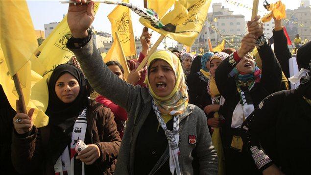 Des jeunes femmes agitent les drapeaux jaunes du Fatah lors d'une manifestation à Gaza pour fêter l'anniversaire du mouvement du président Mahmoud Abbas, le 4 janvier 2013.