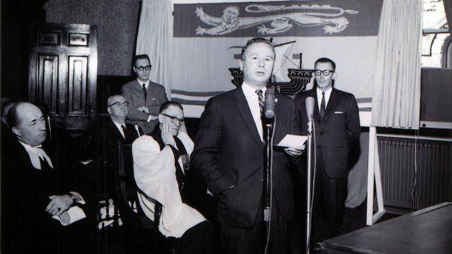 Photo prise à l'Assemblée législative du Nouveau-Brunswick, le 25 mars 1965, lors du dévoilement public du drapeau du Nouveau-Brunswick.  De gauche à droite, Melbourne M. Hoyt, c.r., greffier du Conseil exécutif, le révérend George A. Hatton, pasteur anglican à Fredericton, chapelain de l'Assemblée législative, l'honorable Louis J. Robichaud, c.r., premier ministre, M. Cyril B. Sherwood, chef de l'opposition à l'Assemblée législative.  Derrière, assis, l'honorable Kenneth J. Webber, ministre du Travail et, debout, Robert Pichette, alors chef de cabinet adjoint du premier ministre et concepteur du drapeau.  Collection Archives provinciales du Nouveau-Brunswick.