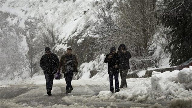 marchent dans une rue enneigée.