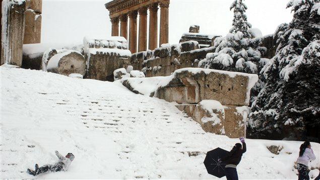 Des enfants s'amusent dans la neige au pied du temple romain de Jupiter, à Baalbek, au Liban.