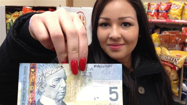 Ali Fontaine tient un billet de cinq dollars modifié