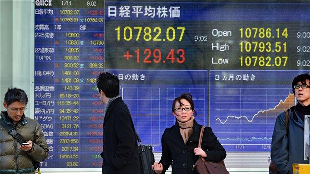 Des Japonais marchent devant un écran montrant les cours de la bourse, alors que le gouvernement vient d'annoncer un plan de relance économique.