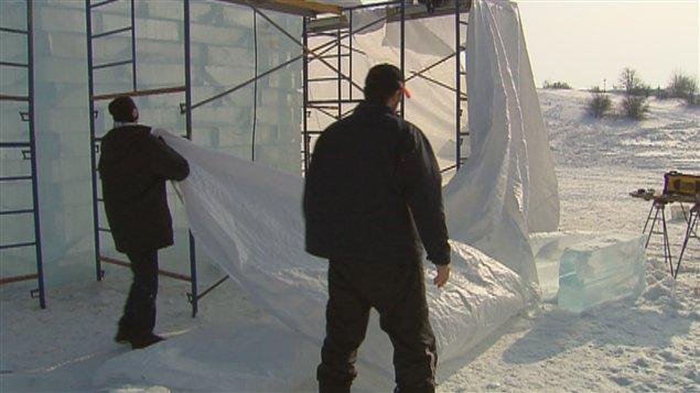 Des ouvriers recouvrent la structure du Palais de Bonhomme.