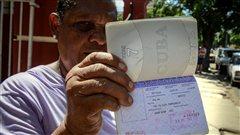 Une Cubaine montre sa carte blanche, un permis de sortie du pays dont les citoyens n'ont d�sormais plus besoin pour sortir du pays