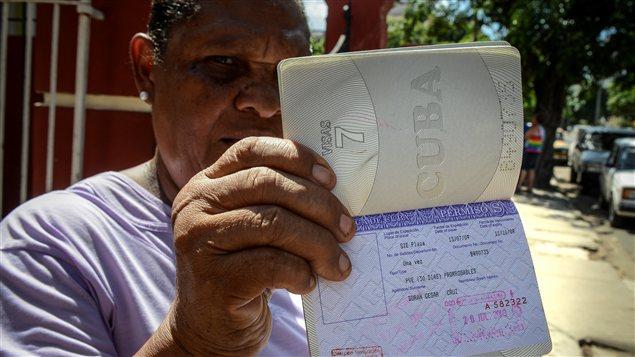 Une Cubaine montre sa carte blanche, un permis de sortie du pays dont les citoyens n'ont désormais plus besoin pour sortir du pays