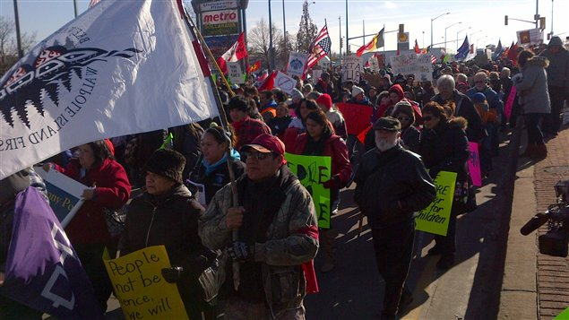 Des manifestants marchent le long du chemin Huron Church à Windsor.