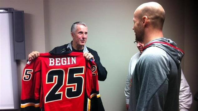 Steve Bégin reçoit son chandail des mains de l'entraîneur-chef des Flames, Bob Hartley.