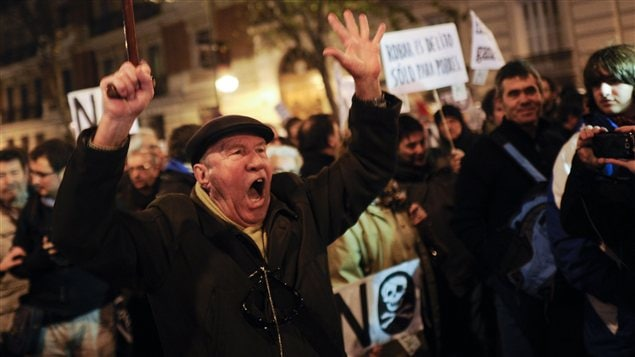 Des manifestants protestent contre les allégations de corruption devant le siège du Parti populaire, à Madrid