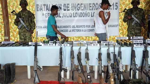 Deux membres de l'Armée de libération nationale (ELN) cèdent leur AK-47 à l'armée colombienne en décembre 2008, à Quibdo, en Colombie.