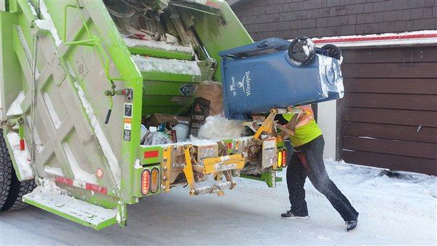 Un employé du service de collecte des déchets de la Ville de Winnipeg est à l'oeuvre malgré le froid glacial, dans le quartier Saint-Boniface, le 22 janvier 2013.