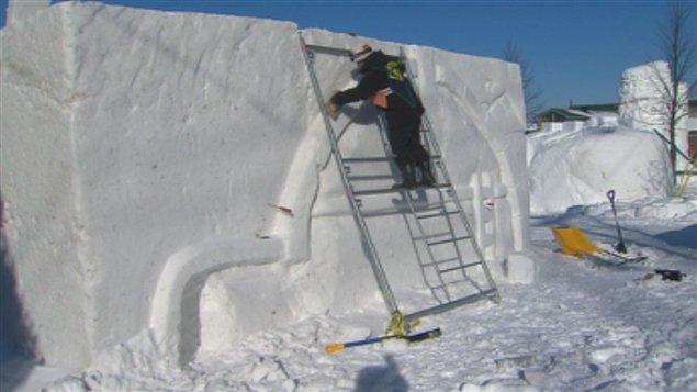 un sculpteur sur neige à l'oeuvre