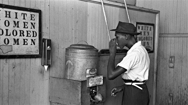 Un homme s'abreuve à une fontaine réservée aux Noirs à Oklahoma, aux États-Unis, en 1939. / © Russell Lee, Library of Congress, Wikipédia