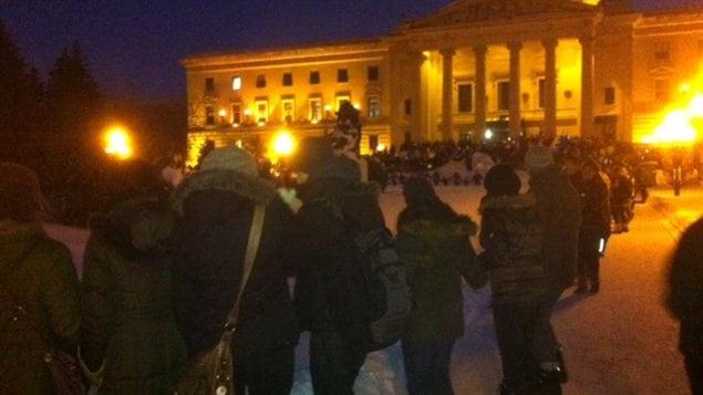 Un grand nombre de personnes prennent part à une danse en cercle devant le palais législatif du Manitoba à Winnipeg, le 28 janvier 2013, dans le cadre du mouvement Idle No More.
