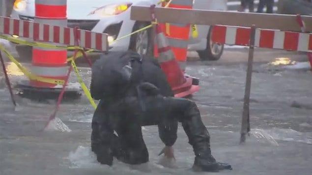 Ce piéton a eu du mal à se frayer un chemin au milieu de la rue inondée.