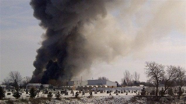 Une épaisse colonne de fumée est visible à distance.