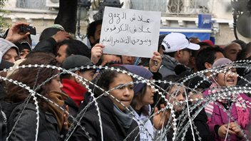Des manifestantes chantent derrière un barbelé devant le ministère de l'Intérieur, à Tunis.