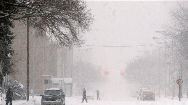 Des gens traversent la rue à Muskegon au Michigan le 7 février. Il neige depuis jeudi dans cette région.