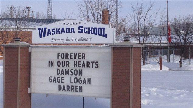 Le drapeau est en berne à l'école de Waskada, le 11 février 2013, et une inscription rend hommage aux disparus dans un accident d'avion survenu la veille, près de cette communauté du sud-ouest manitobain.
