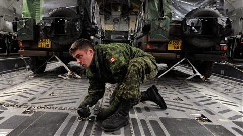 Un militaire canadien s'assure de bien immobiliser des jeeps à l'intérieur d'un avion de transport.